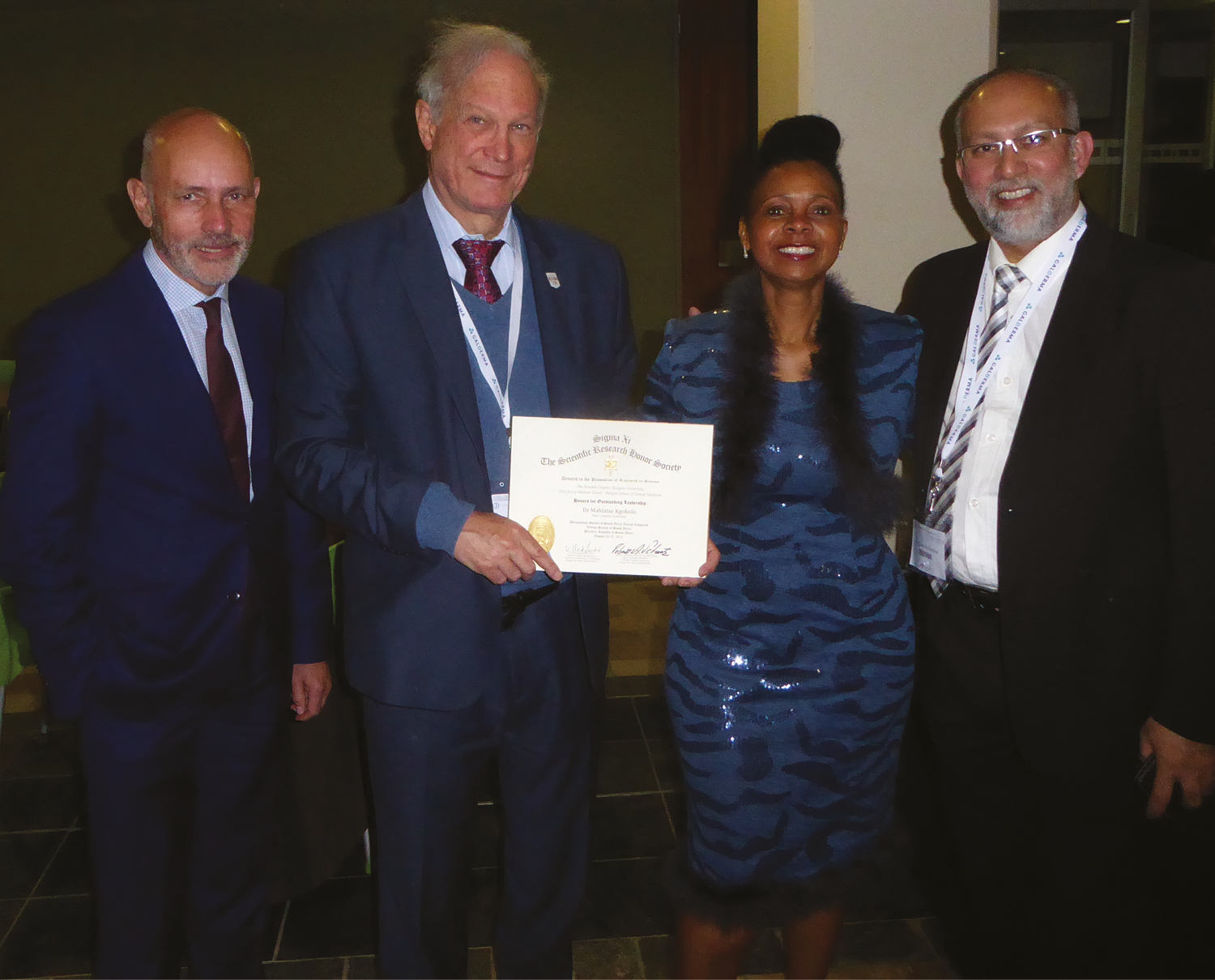 Figure 1: Conference Committee Chairs Mahlatse Kgokolo and Noufal Raboobee, who is also Vitiligo Society of South Africa President, are honored by Prof. Robert A. Schwartz with a Sigma Xi leadership recognition award, appreciated by Prof. Christopher EM Griffiths